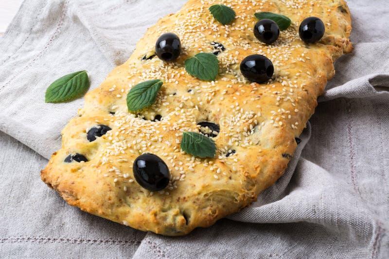 Focaccia del pan italiano con la aceituna, el ajo y las hierbas en el lino fotos de archivo libres de regalías