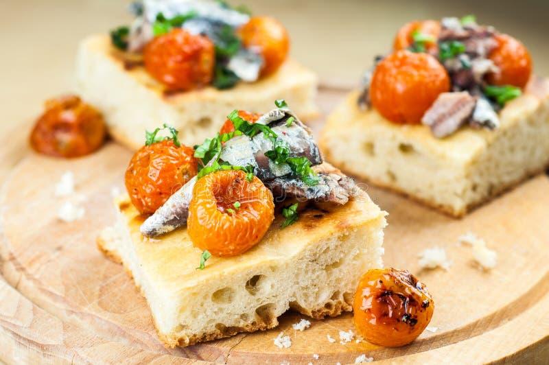 Focaccia deliziosa con le sardine ed i pomodori ciliegia immagini stock
