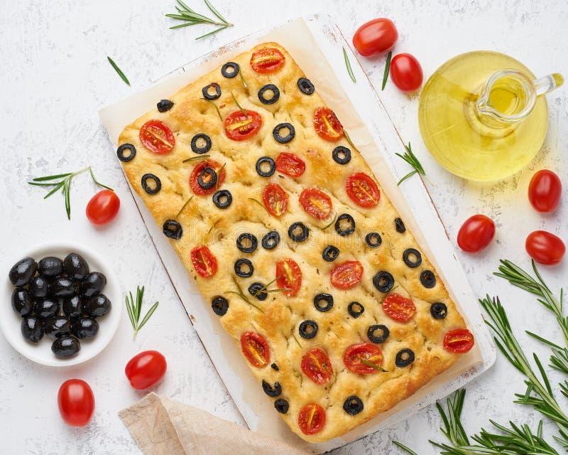 Focaccia med tomater, oliv och rosmarin, b?sta sikt Helt italienskt plant br?d, flaska med olja royaltyfri foto