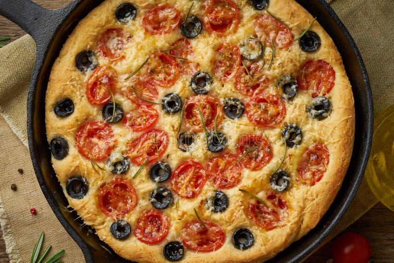 Focaccia pizza i kastrull Slut upp italienskt plant br?d med tomater, oliv och rosmarin B?sta sikt, tr?tabell arkivbilder