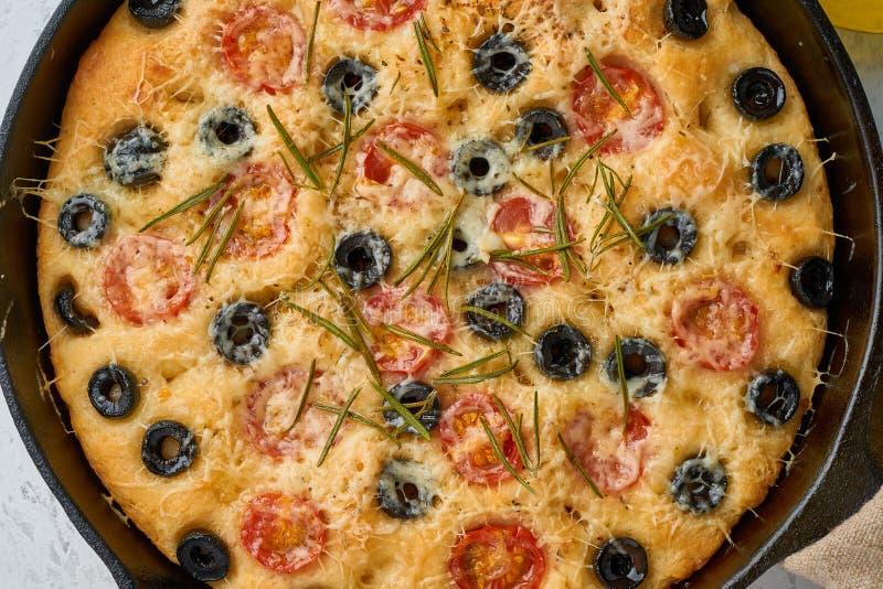 Focaccia pizza i kastrull Slut upp italienskt plant br?d med tomater, oliv och rosmarin B?sta sikt, vit konkret bakgrund arkivfoto