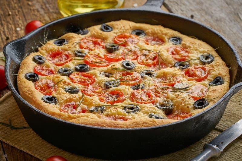 Focaccia pizza i kastrull Slut upp italienskt plant br?d med tomater, oliv och rosmarin Sidosikt, tr?tabell fotografering för bildbyråer