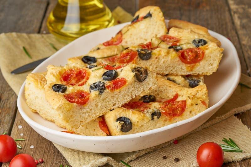 Focaccia pizza i platta med tomater, oliv och rosmarin Huggit av italienskt plant br?d Sidosikt, tr?tabell royaltyfria bilder