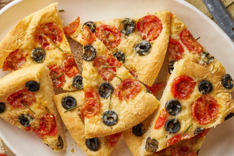 Focaccia pizza i platta med tomater, oliv och rosmarin Huggit av italienskt plant br?d T?tt upp, tr?tabell arkivfoto