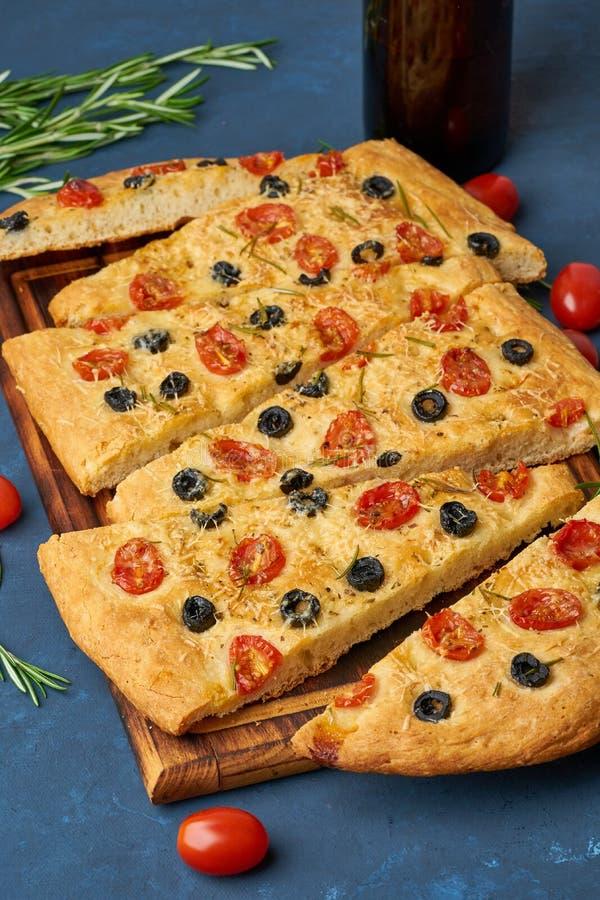 Focaccia, pizza, italienskt plant bröd med tomater, oliv och rosmarin Mörkt - blå bakgrund, sidosikt arkivfoto