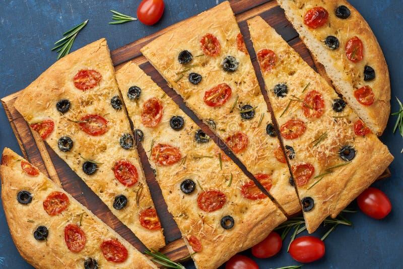 Focaccia, pizza, pan plano italiano con los tomates, aceitunas y romero en la tabla azul marino, visión superior fotografía de archivo