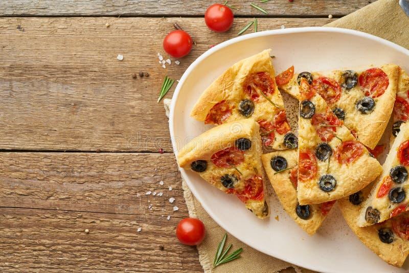 Focaccia, pizza, skivor av italienskt plant bröd med tomater, oliv och rosmarin på den trälantliga tabellen, kopieringsutrymme royaltyfri bild