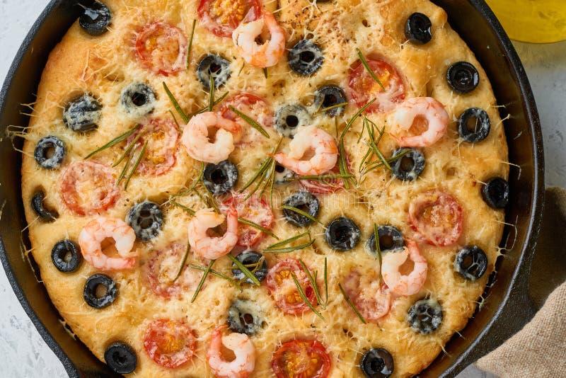 Focaccia r?kapizza i kastrull Slut upp italienskt plant br?d med tomater, oliv och rosmarin B?sta sikt, vit betong royaltyfri fotografi
