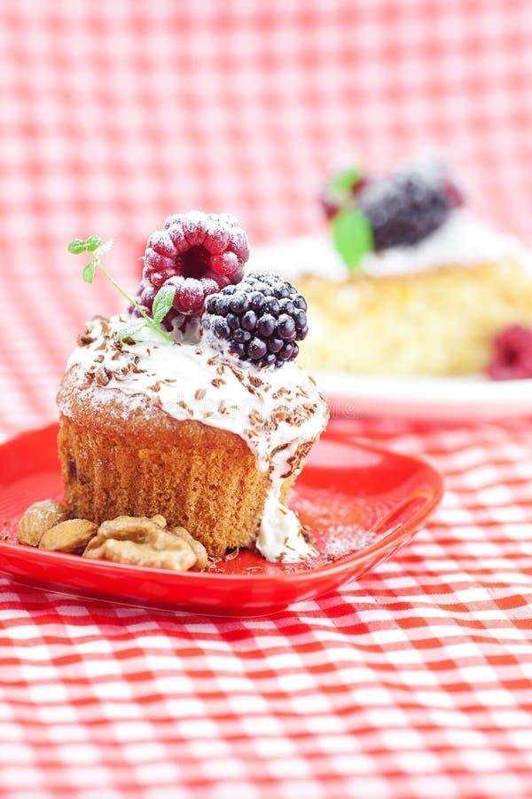 Focaccina con crema e la torta sbattute con glassa fotografia stock
