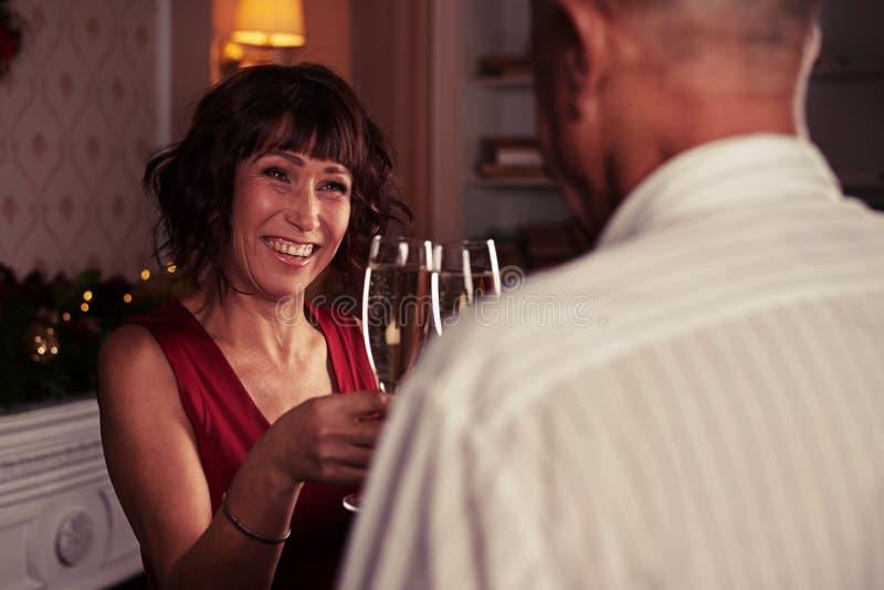 Focalize no tinido superior feliz da mulher um glasse do champanhe com fotografia de stock