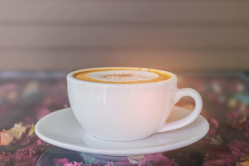 Foco borrado e macio do delicado abstrato um o copo do cappuccino, café quente com a luz do feixe, fundo do tom do efeito do alar fotos de stock