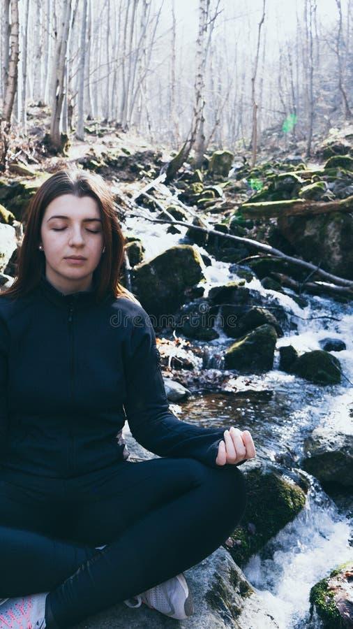 Foco cerrado de la chica joven de los ojos que hace el loto de la actitud de la yoga que se sienta en una roca en un río que medi fotografía de archivo libre de regalías