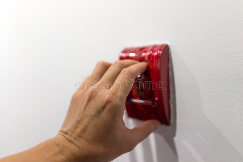 Foco de Selectived disponível que puxa o alarme de incêndio na parede branca para o ato foto de stock