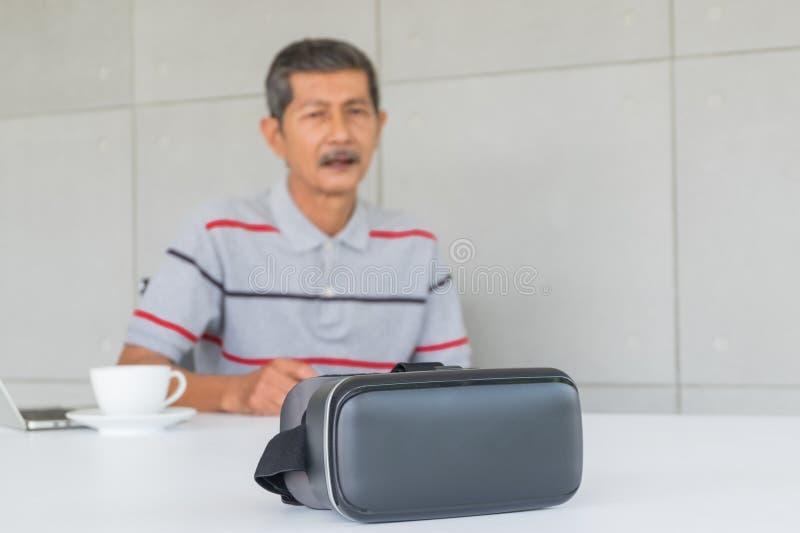 Foco de vidros de VR com o homem superior asiático para a tecnologia moderna foto de stock royalty free