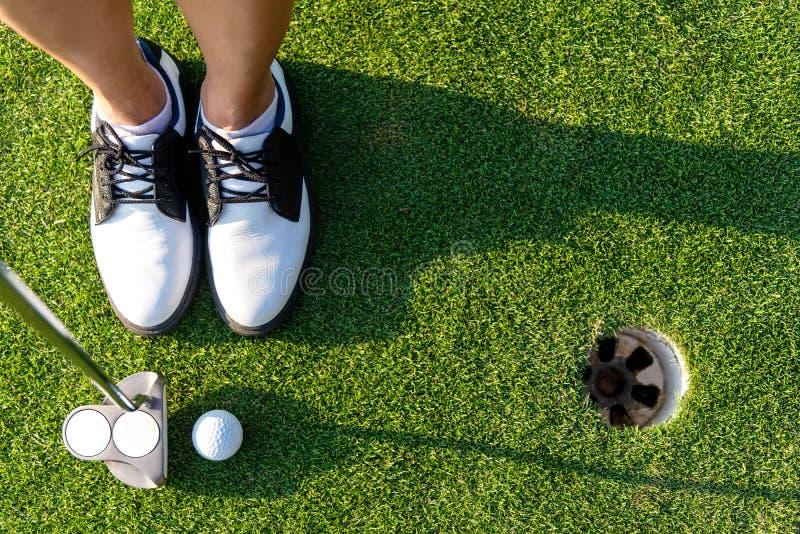Foco deportivo asiático de la mujer del golfista de la visión superior que pone la pelota de golf en el golf verde foto de archivo