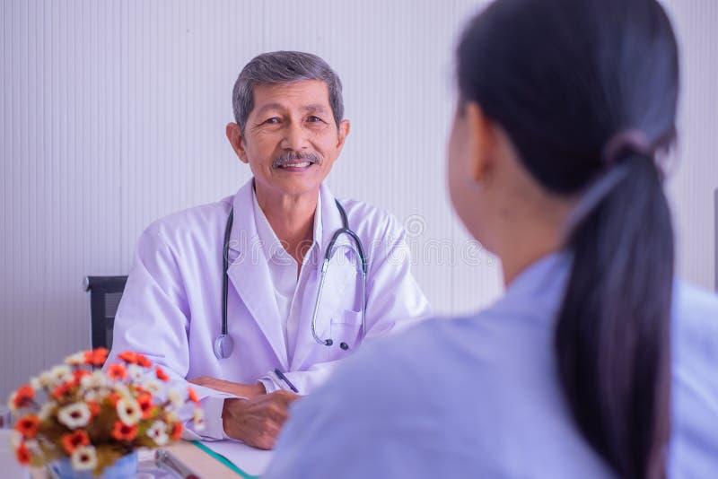 Foco do doutor asiático do homem superior Sorrindo, com o assento paciente da mulher que fala no hospital do escritório imagens de stock