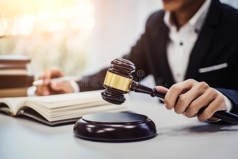 Foco do martelo de madeira na tabela com o advogado masculino no fundo justiça e lei, advogado, juiz da corte, conceito fotos de stock royalty free