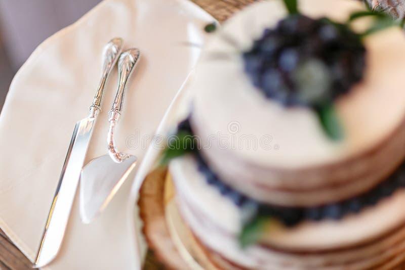 Foco en el cuchillo y la cuchilla Boda o torta de cumpleaños con las bayas Empanada dulce en banquete en restaurante foto de archivo