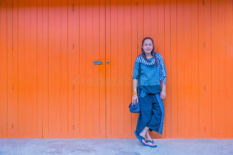 Foco macio abstrato a mulher que está na frente da parede de madeira velha com a luz natural foto de stock
