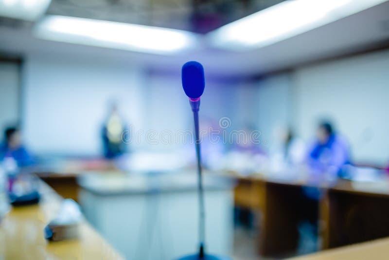 Foco macio de microfones sem fio desktop da conferência com unidade de negócio obscura em uma sala de reunião, microfone na mesa  fotos de stock royalty free