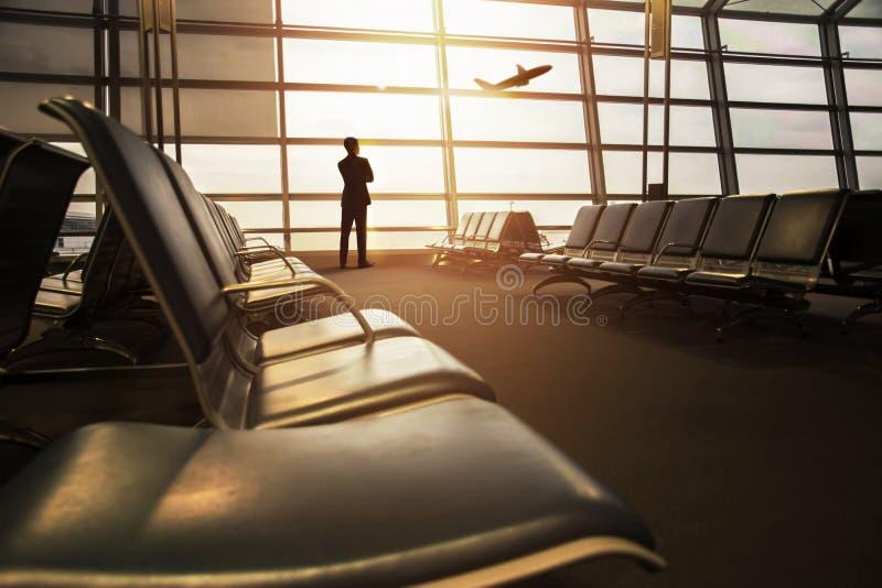 Foco macio do homem de negócios em sua viagem de negócios que olha Airpla fotografia de stock royalty free