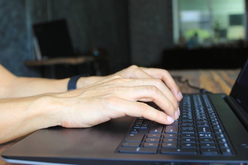 Foco macio do homem novo do freelancer que trabalha usando o laptop no escritório domiciliário, na tecnologia de comunicação e no fotografia de stock royalty free