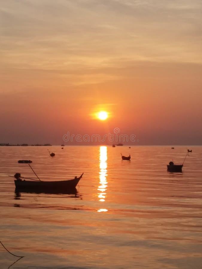 Foco macio, por do sol da silhueta no mar com os barcos de pesca pequenos imagem de stock royalty free