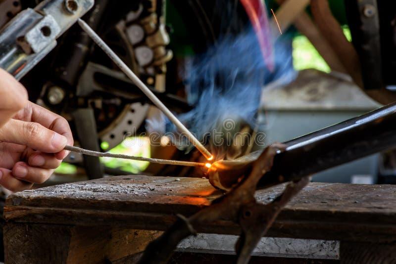 Foco na haste e no borrão de movimento de aço Imagem da luminosidade reduzida do soldador ou do artesão imagens de stock royalty free