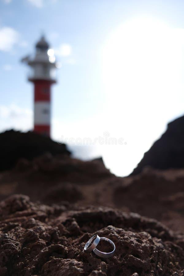 Foco nas alianças de casamento na rocha vulcânica com o farol vermelho e branco borrado no fundo imagens de stock royalty free