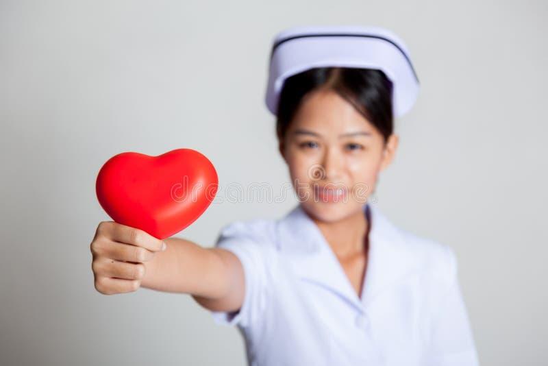 Foco rojo del corazón de la demostración asiática joven de la enfermera en el corazón imagen de archivo