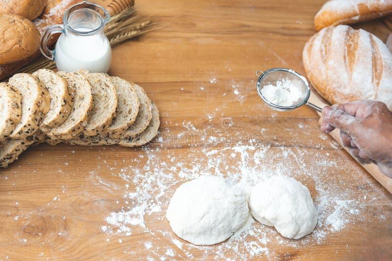 Foco seleccionado en la cocina que prepara una pasta en fondo de madera con la harina, leche para hacer el pan y el bollo imagen de archivo libre de regalías