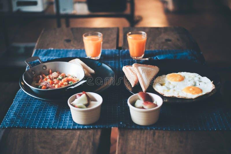 Foco selecionado, café da manhã na tabela de madeira com sanduíche, ovo frito e laranja imagens de stock royalty free