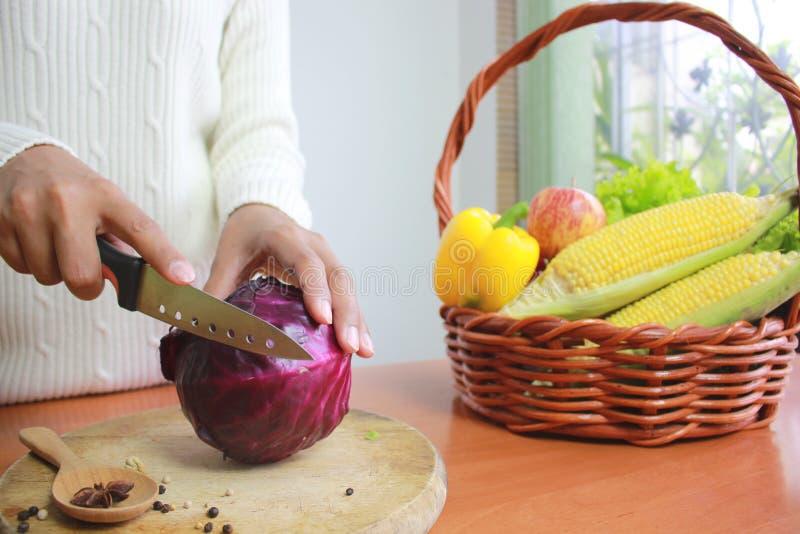 Foco selectivo de la coliflor y de la verdura del corte de la mujer joven en tabla de cocina fotos de archivo
