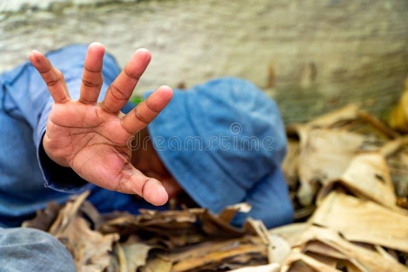 Foco selectivo de la mano sucia sin hogar en casa abandonada ?l que ?l intent? aumentar su mano para prevenir peligro de abusos f fotos de archivo libres de regalías