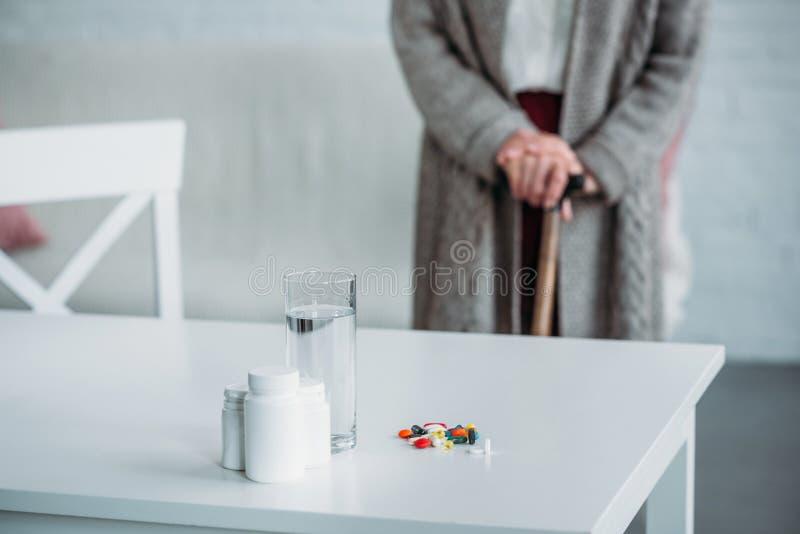 foco selectivo de la mujer mayor con el bastón que se coloca en sitio con las medicinas y el vidrio de agua en el tablero de la m foto de archivo libre de regalías