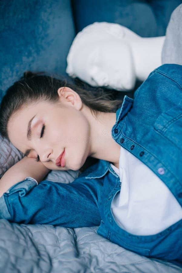 foco selectivo de la mujer que duerme cerca de maniquí en la cama no recompensada foto de archivo