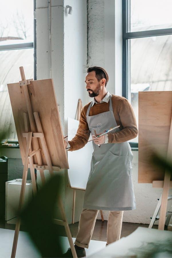 foco selectivo de la pintura masculina madura del artista en el caballete imágenes de archivo libres de regalías