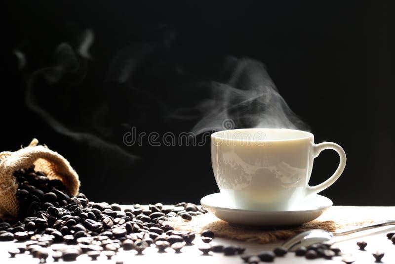 Foco selectivo de la taza y de las habas de café con el humo que sube en dar imagenes de archivo