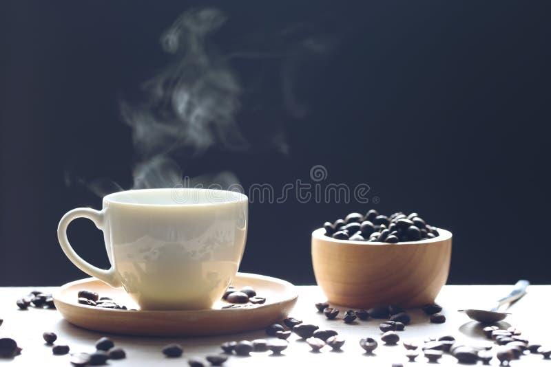 Foco selectivo de la taza y de las habas de café con el humo que sube en dar foto de archivo libre de regalías