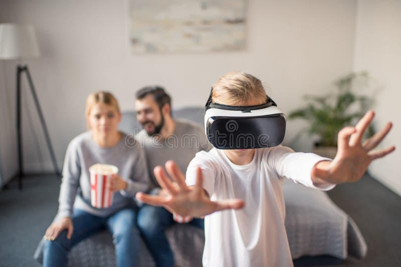 foco selectivo de padres con las palomitas que miran al niño que juega en auriculares del vr foto de archivo libre de regalías