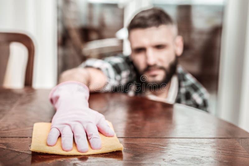 Foco selectivo de una mano masculina en un guante de goma imagenes de archivo