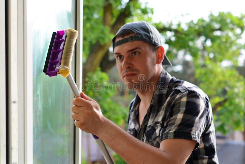 Foco selectivo de una ventana de la limpieza del hombre joven con la fregona Lavadora de ventana Compañía profesional de la limpi foto de archivo libre de regalías