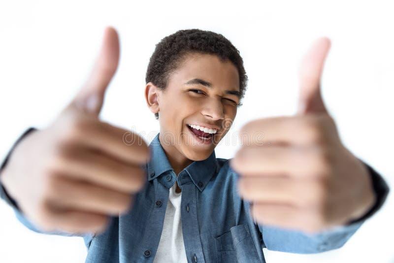 foco selectivo del adolescente afroamericano feliz que muestra los pulgares para arriba imagen de archivo