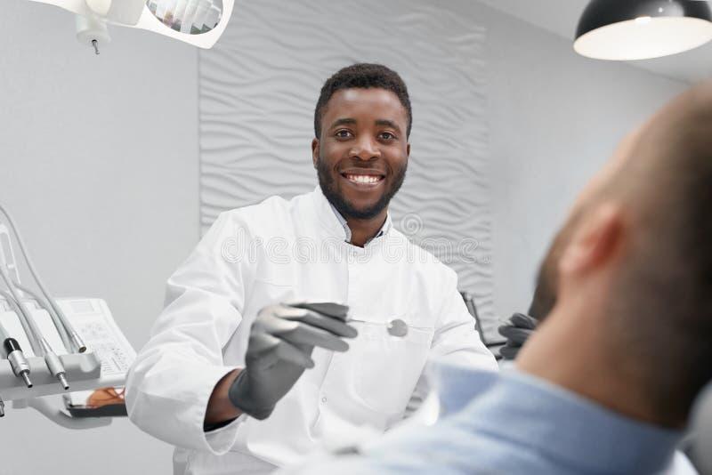 Foco selectivo del dentista de sexo masculino en vías del curado de los dientes fotografía de archivo