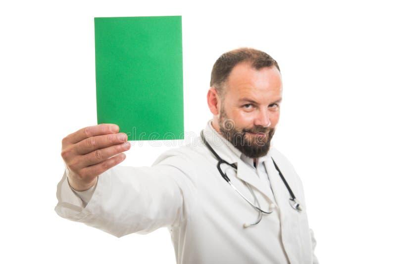 Foco selectivo del doctor de sexo masculino que sostiene la cartulina verde imágenes de archivo libres de regalías