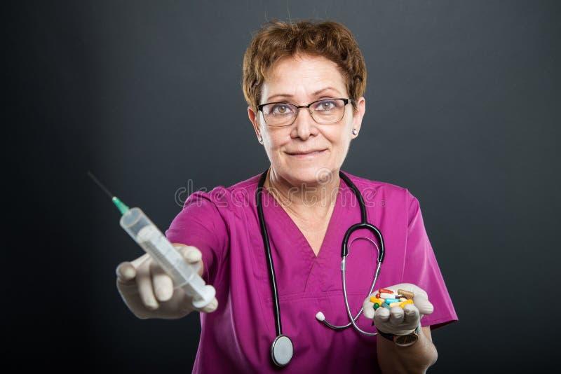 Foco selectivo del doctor mayor de la señora que sostiene la jeringuilla y píldoras imagenes de archivo