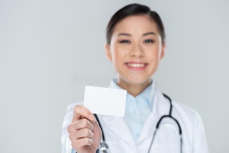 Foco selectivo del doctor sonriente que muestra la tarjeta en blanco a disposición imagen de archivo libre de regalías