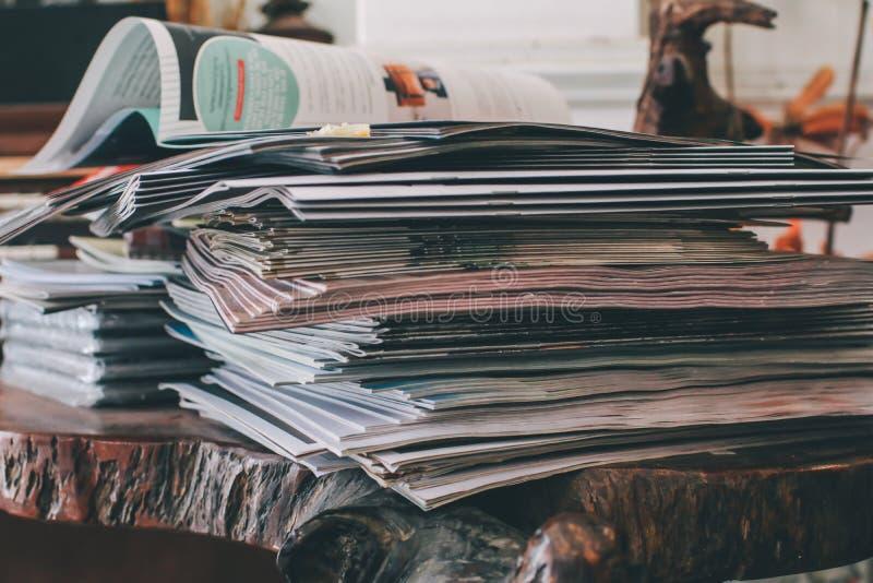 Foco selectivo del lugar de amontonamiento de la revista en la tabla en sala de estar foto de archivo libre de regalías