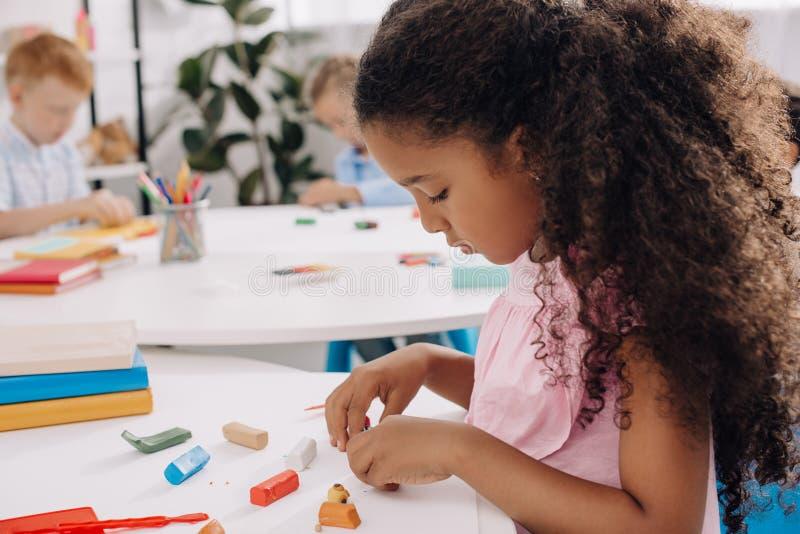 foco selectivo del niño afroamericano con el plasticine que esculpe la figura en la tabla imagenes de archivo