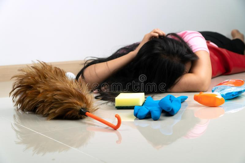 Foco selectivo del plumero de la pluma Las amas de casa asiáticas mienten en el piso debido cansarse de tareas de hogar Con el di fotos de archivo libres de regalías